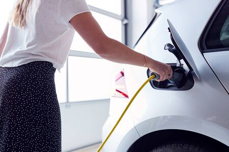 Close Up Of Woman Charging Electric Vehicle With Cable In Garage At Home