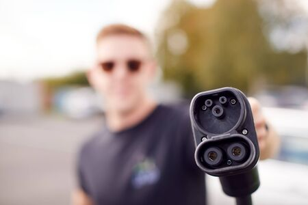 Man Holding Power Charging Cable For Electric Car In Outdoor Car Park
