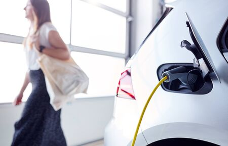 Woman Going Shopping Whilst Leaving Electric Vehicle To Charge In Car Park 스톡 콘텐츠