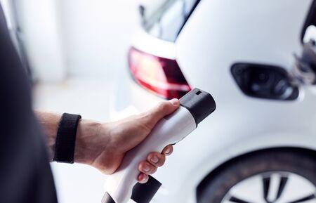 Nahaufnahme der Hand, die das Stromkabel an ein umweltfreundliches emissionsfreies Elektroauto anbringt