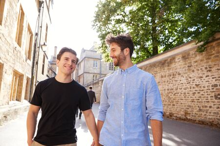 Loving Male Gay Couple On Vacation Holding Hands Walking Along City Street Stock Photo