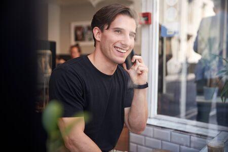 Young Man In Coffee Shop Talking On Mobile Phone Viewed Through Window