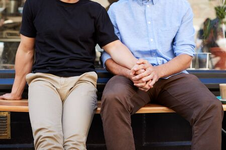 Close Up Of Male Gay Couple Sitting Outside Coffee Shop Holding Hands Stock Photo