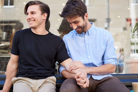 Loving Male Gay Couple Sitting Outside Coffee Shop Holding Hands