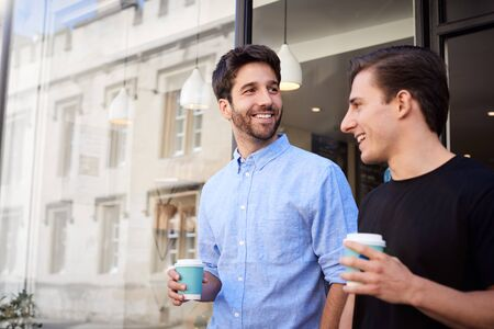 Male Gay Couple On Date Coming Out Of Coffee Shop Together