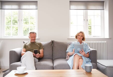 Anti-Social Senior Couple Sitting On Sofa At Home Using Digital Tablet And Mobile Phone