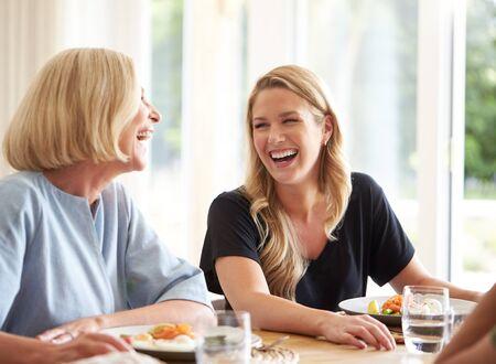 Famille avec mère aînée et fille adulte mangeant un brunch autour d'une table à la maison ensemble