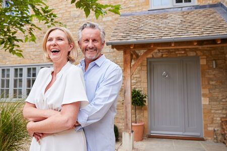 Portrait Of Senior Couple Standing Outside Front Door Of Home