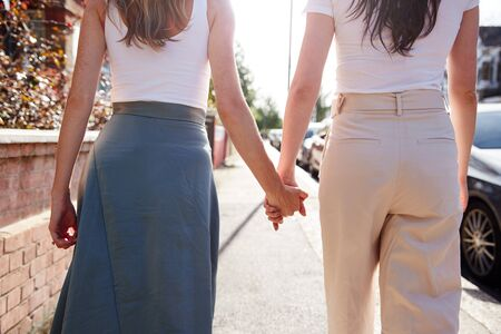 Close Up View Of Same Sex Female Couple Holding Hands As They Walk Along Road From Behind Stok Fotoğraf