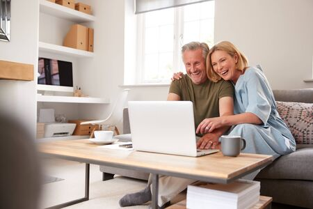Senior Couple Sitting On Sofa In Lounge At Home Using Laptop Together