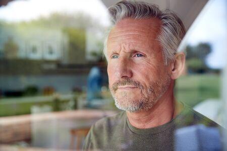 Concerné Senior Man Standing et à la porte de la cuisine vue à travers la fenêtre