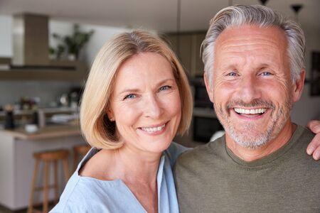 Retrato, de, sonriente, pareja mayor, posición, en casa, en, cocina, juntos