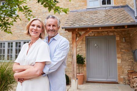 Porträt eines älteren Paares, das vor der Haustür des Hauses steht