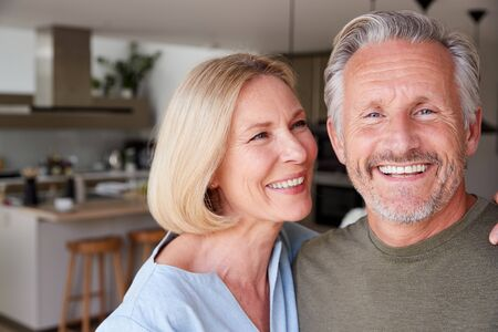 Portrait Of Smiling Senior Couple Standing At Home In Kitchen Together