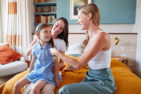 Same Sex Female Couple At Home Getting Daughter Ready For School Plaiting Her Hair