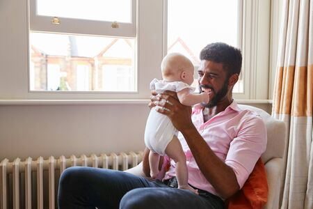 Loving Father Playing With Smiling Baby Daughter At Home Stock Photo