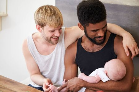 Loving Male Same Sex Couple Cuddling Baby Daughter At Home Together