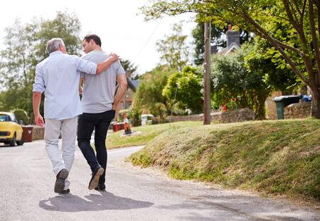 Rear View Of Senior Father With Adult Son Talking As They Walk Along Country Road Together 스톡 콘텐츠