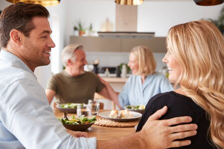 Introducing Boyfriend Or Girlfriend To Senior Parents At Meal Around Table At Home Together Stock Photo