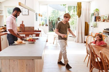 Same Sex Male Couple With Daughter Making Breakfast At Home Together