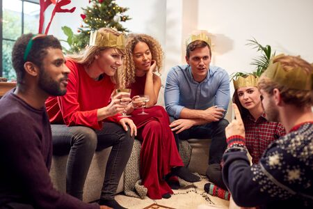 Group Of Friends Playing Charades After Enjoying Christmas Dinner At Home