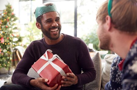 Gay Male Couple At Home Exchanging Gifts On Christmas Day Together Stock Photo