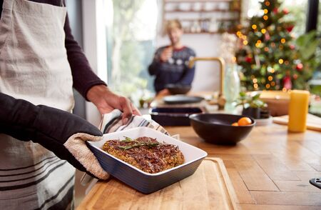 Close Up Of Man Taking Vegetarian Nut Roast Out Of Oven For Christmas Dinner