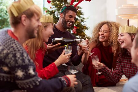 Group Of Friends Celebrating With Champagne After Enjoying Christmas Dinner At Home