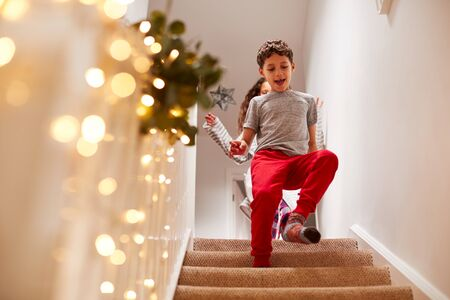 Excited Children Running Downstairs To Open Presents On Christmas Morning