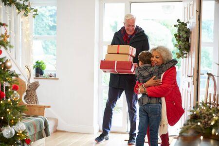 Aufgeregter Enkel grüßt Großeltern mit Geschenken zu Besuch am Weihnachtstag