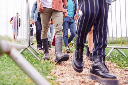 Close-up van vrienden bij de ingang van het muziekfestival die door veiligheidsbarrières lopen