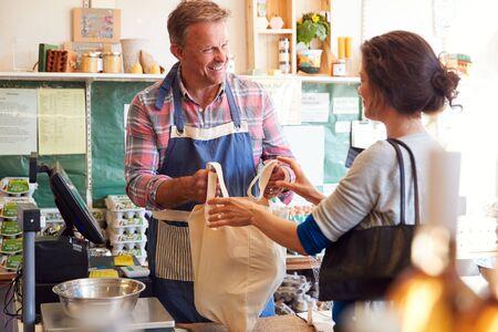 Asistente de ventas que atiende al cliente femenino en la caja de la tienda de la granja orgánica