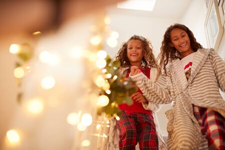 Excited Girls Running Downstairs To Open Presents On Christmas Morning Stock Photo