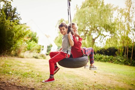 Brother And Sister Playing In Tire Swing In Garden At Home