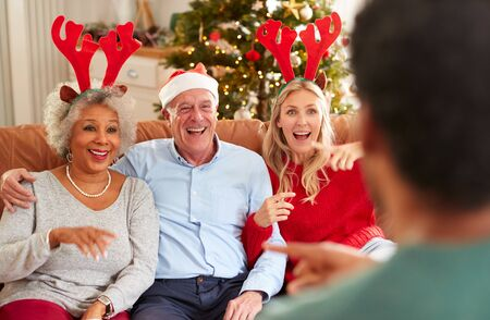 Adult Family Sitting On Sofa Playing Game Of Charades At Christmas Together
