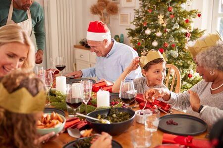 Father Serving Food At Multi-Generation Family Christmas Meal At Home Imagens