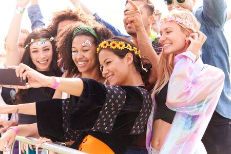 Young Friends In Audience Behind Barrier At Outdoor Music Festival Posing For Selfie