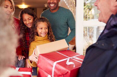 I nonni arrivano con i regali per festeggiare il Natale in famiglia multigenerazionale a casa