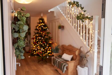Pasillo de la casa decorada para Navidad visto a través de la puerta delantera