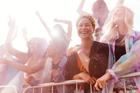 Audiencia con humo de colores detrás de la barrera bailando y cantando en el festival al aire libre disfrutando de la música Foto de archivo