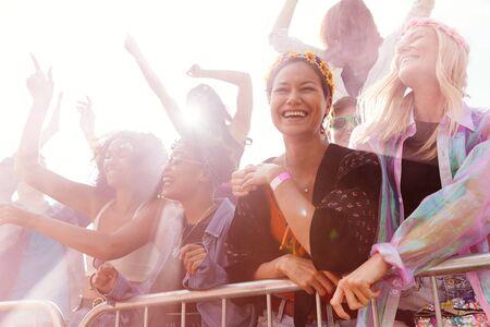 Publiczność z kolorowym dymem za barierą tańczy i śpiewa na festiwalu na świeżym powietrzu, ciesząc się muzyką Zdjęcie Seryjne