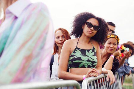 Grupo de jóvenes amigos esperando detrás de la barrera en la entrada al sitio del festival de música