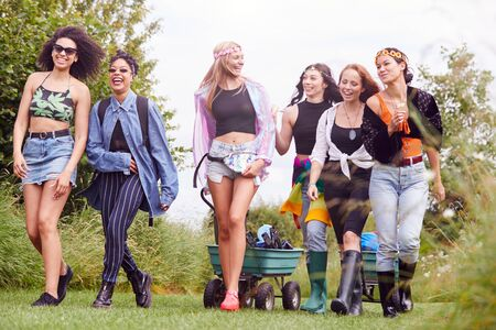 Group Of Excited Young Friends Carrying Camping Equipment Through Field To Music Festival