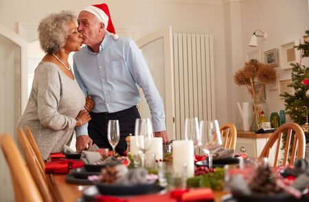 Loving Senior Couple At Home Setting And Decorating Table For Meal On Christmas Day