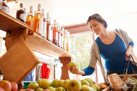 Kundin mit Warenkorb Kauf von frischen Äpfeln im Bio-Bauernhof-Shop Standard-Bild
