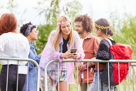 Young Woman Looking At Mobile Phone As She Waits Behind Barrier At Entrance To Music Festival Site