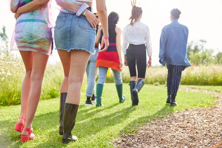Close Up Rear View Of Female Friends Walking Back To Tent After Outdoor Music Festival