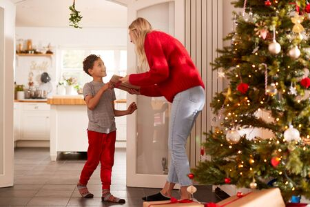 Son Giving Mother Gift On Christmas Morning At Home Stock Photo