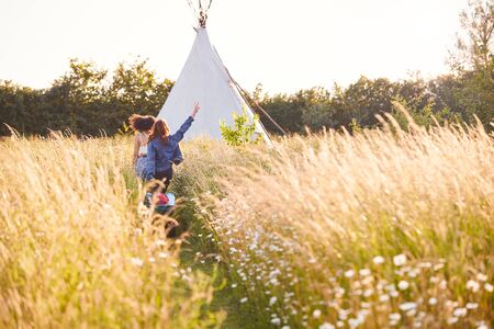 Two Female Friends Walking Pulling Trolley Through Field Towards Teepee On Summer Camping Vacation