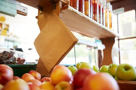 Paper Bags Hanging Over Fruit And Produce Displayed In Organic Farm Shop